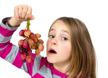 Little girl with grapes Stock Images