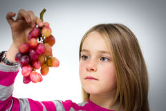 Little girl with grapes Stock Photos