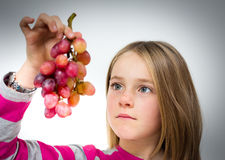 Little girl with grapes Stock Photo