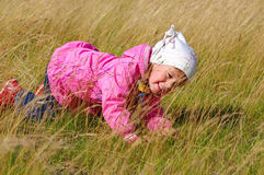 LITTLE GIRL IN THE GRASS. Stock Photo