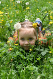 Little girl on grass. Smiley little girl lie over grass with flowers Royalty Free Stock Photo