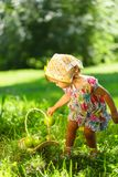 Little girl on grass with basket of apples Stock Image
