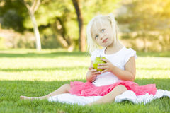 Little Girl In Grass Eating Healthy Apple Royalty Free Stock Images