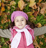 Little girl at grass and leafs in the park. Royalty Free Stock Image