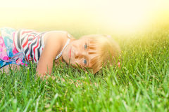 Little girl on the grass Stock Photos