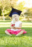Little Girl In Grass Wearing Graduation Cap Holding Diploma With Royalty Free Stock Images