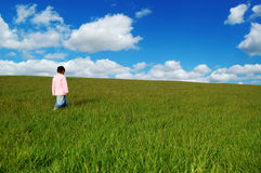 Little girl in grassy field Stock Photo