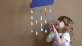 Little girl on gray background play with drop shapes and cloud stock footage