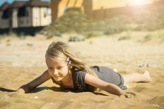 Beautiful girl in the sun on the sand of the sea. Royalty Free Stock Image