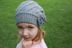 Little girl in gray hat and pink sweater Stock Photos