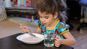 Little girl greedily eating semolina porridge. Wash down with water from a transparent glass. stock video