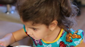 Little girl greedily eating semolina porridge. Wash down with water from a transparent glass. closeup. stock footage