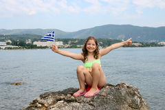 Little girl with Greek flag and thumb up on summer vacatio Stock Image