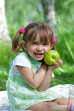 Little girl with green apple outdoor summertime Stock Photo