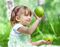 Little girl with green apples outdoor summertime Stock Image