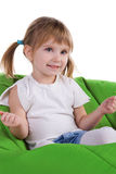 Little girl on a green armchair Stock Photo
