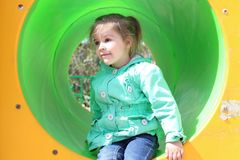A little girl in a green coat carelessly plays in a multi-colored plastic pipe. Safe playgrounds for the joy of children and parents. A little girl in a green Stock Images