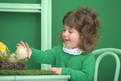Little girl in a green dress. With chicken Royalty Free Stock Image
