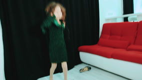 Little girl in green dress and her mother`s shoes, dancing. stock video