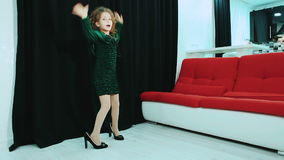 Little girl in green dress and her mother`s shoes, dancing. stock footage
