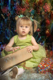 Little girl with green dress with pigtails sitting Stock Photography