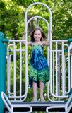 Little girl in green dress on playground. Little girl in green dress poses with a smile on a local playground Royalty Free Stock Photos