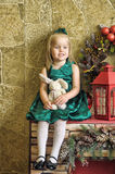 Little girl in a green dress with a toy hare Royalty Free Stock Images