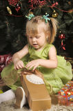 Little girl in a green dress  under the Christmas tree Royalty Free Stock Images
