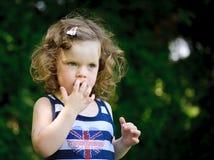 Little girl in a green field Stock Photos
