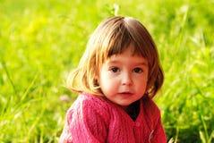 Little girl on green grass Stock Image