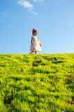 Little girl on a green grass hill Stock Images