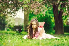 Little girl on green grass with petals stock photo