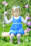 Little girl on green grass in the spring in a Blue Dress Stock Photography