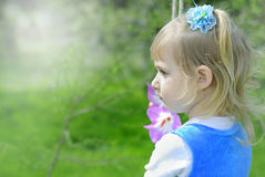 Little girl on green grass in the spring in a Blue Dress Royalty Free Stock Photos