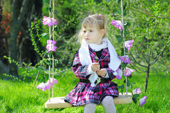 Little girl on green grass in the spring on a swing Stock Photography