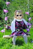 Little girl on green grass in the spring on a swing Royalty Free Stock Images