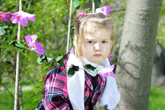 Little girl on green grass in the spring on a swing Stock Photo