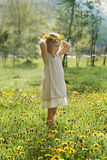 Little girl on green grass and summer flowers outdoors Royalty Free Stock Image