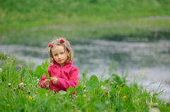 The little girl is on the green grass by the water. The child looks seriously at the lens. Concentrated look, curly hair Royalty Free Stock Photography