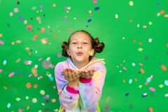 A little girl on a green isolated background in a bright suit blows away a streamer. Space for text. The concept of a holiday,