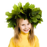 Little girl with green maple leaves on the head Stock Images