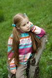 A little girl on a green meadow. Dressed warmly in a cold summer day Stock Images