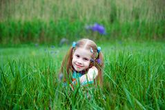 A little girl on a green meadow. Dressed warmly in a cold summer day Royalty Free Stock Photos