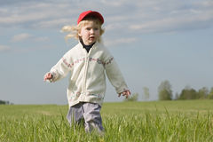 Little girl on green meadow Stock Images