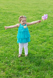 Little girl among green meadow with flowers Royalty Free Stock Images