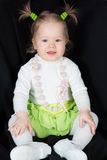 Little girl in a green skirt with funny scrunchy. On the head royalty free stock image