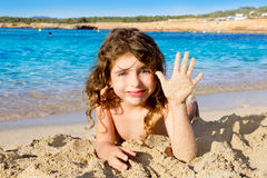 Little girl greeting hand gesture in sandy beach Royalty Free Stock Photos