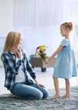 Little girl greeting her mother with flowers at home Stock Image