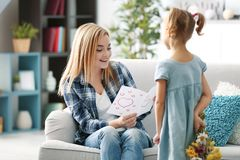 Little girl greeting her mother at home Stock Photo