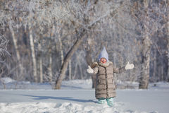 Little girl in grey jacket plays with snow in winter forest Stock Photography